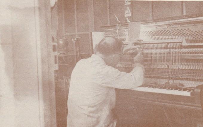 François Delmas, 78 ans réparant un piano dans son atelier